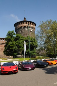 A row of multi-coloured Lamborghinis next to the Castello Sforzesco.