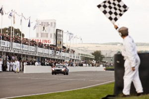 Formula 1 test driver Giedo van der Garde and David Hart cross the finish line in the latter AC Cobra during the RAC TT Celebration race at the 2014 Goodwood Revival.