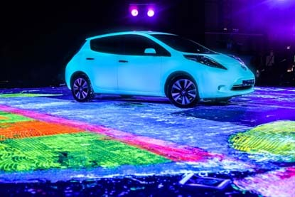 Artist Ian Cook used the tires of the Nissan LEAF to drive glow-in-the-dark paint across the surface of the canvas