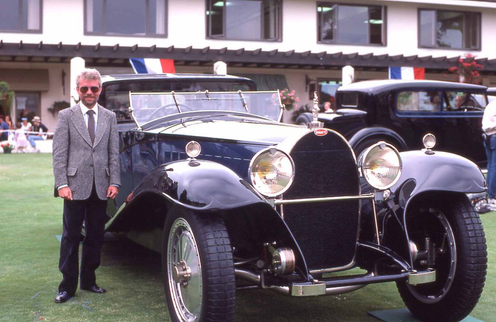 Derek Bell standing beside the famed Coupe Napoleon at Pebble Beach in 1985.